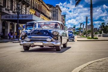 HDR - Schwarzer Oldtimer mit weißem Dach fährt auf der Hauptstraße an der historischen Häuserfront vorbei - Serie Kuba Reportage