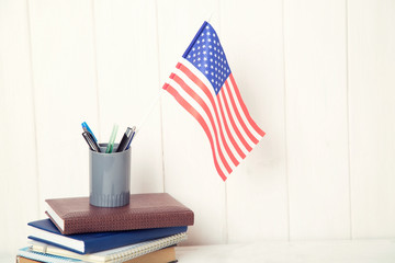 Books and the US flag on the desk. English language learning. Flag the United States of America.