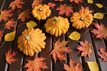 Orange squashs, red and yellow autumn leaves on a brown wooden background, top view