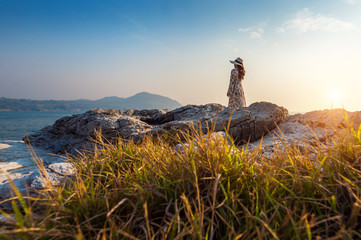 Wall Mural - Young woman standing on the top of rock at sunset in Si chang island.