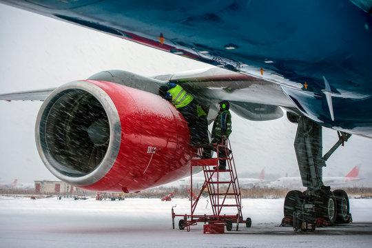 Airplane mechanics checking jet engine if civil aircraft