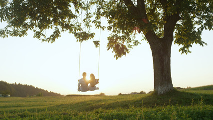 LENS FLARE SILHOUETTE: Setting sun shining over young couples shoulders on swing