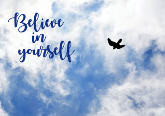Believe in yourself.Motivation inspirational quote on blue sky with clouds and flying bird  background.Selective focus.
