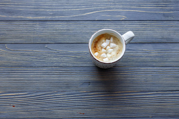 Cup of coffee with marshmallow on a wooden background.