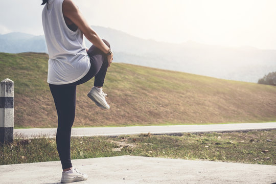 Athlete woman doing some stretching exercises legs before running on outdoor