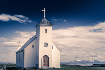 Papiers peints Edifice religieux Flateyjarkirkja white lutheran church with meadow in foreground and sea fjord with dark blue sky and mountains in the background, Flatey, Iceland