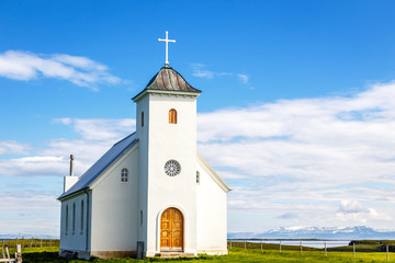 Flateyjarkirkja white lutheran church with meadow in foreground and sea  fjord with blue sky and mountains in the background, Flatey, Iceland