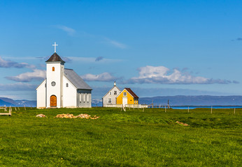 Photo sur Aluminium Edifice religieux Flateyjarkirkja white lutheran church and couple of living huts with meadow in foreground and sea fjord with blue sky in the background, Flatey, Iceland