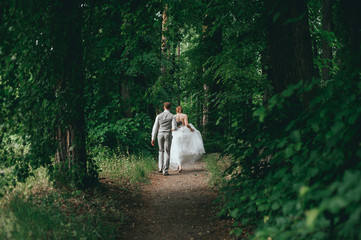 bride and groom posing for a walk in the woods