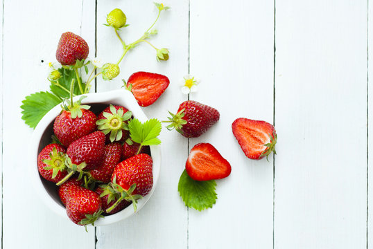 fresh ripe and under ripe strawberry fruits, flowers, leaves on white wood table background