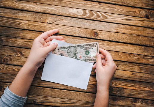 A money note in a white envelope. A person takes out dollars from an envelope.