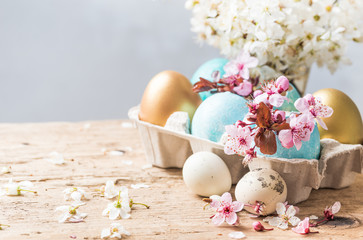Easter holiday background, greeting card.Easter colored eggs and spring flowers on rustic wooden table background copy space.