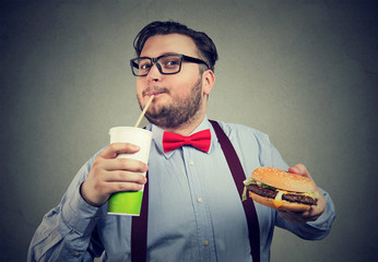 Excited overweight man eating fast food