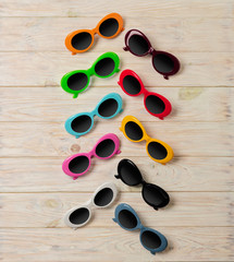Collection of fashionable multi-colored sunglasses - a trend of summer on wooden background.