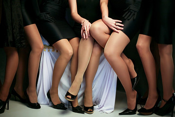 Crop shot of group of women with fit legs wearing black heels and dresses standing together.