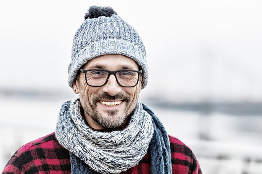 Portrait of urban man in winter knitted wear. Portrait of man in glasses and knitted white-blue scarf and hat. Portrait of happy man. Smiled non shaved guy on outdoor background