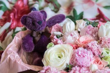 teddy bear in lots of fresh beautiful flowers