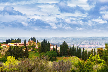 Wall Mural - Traditional Tuscan landscape. Cypress and green hills against the blue cloudy sky. Italy, Europe. Tuscany is popular travel destination.