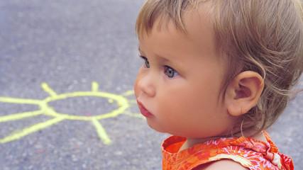 Side view little girl is sitting on the asphalt. Chalk painted sun is on the asphalt behind her shoulder.