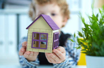 Hands of the boy holding the plastic figure of house. Real estate and family home security concept.