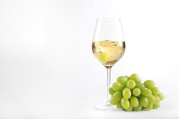 Weiswein in einem Glas mit einer Traube im Glas und Weintrauben nebenliegend