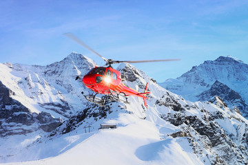 Photo sur Plexiglas Hélicoptère Red helicopter flying in winter Swiss Alps mountain under snow Mannlichen in winter