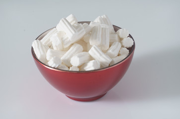 A red plate wit marshmallows on a white background. Close up. Christmas photo.