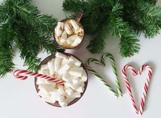 Christmas background, greeting card with a Cup of coffee or chocolate with marshmallows, lollipops, a red plate and tree branches