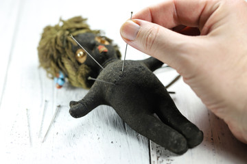vintage voodoo doll on wooden background