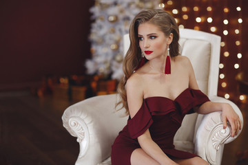 Beautiful sexy lady in an elegant burgundy dress. Close up fashion portrait of model indoors. Beauty brunette woman. Attractive woman in an open dress, posing alone, sitting in a posh white armchair