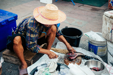 Seller cut a fresh river fish in Local Thailand morning market a traditional fish shop