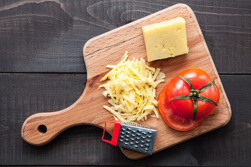 Cutting board with and grater cheese on wooden background. Top view.