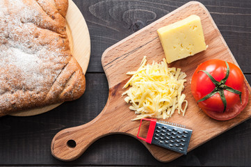Bread and cutting board with and grater cheese on wooden background. Top view.