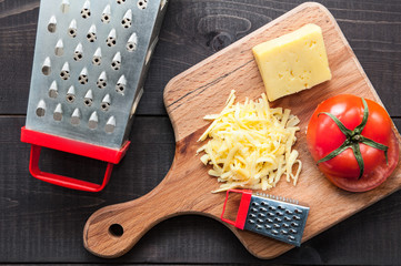 Grater, tomato and cutting board with grater cheese on wooden background. Top view.