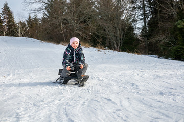 Winter snow activity. Front view of a girl riding a sledge downhill surrounded by trees.