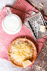 Ingredients for pasta dish or pizza - milk, freshly grated parmesan cheese on a wooden table, and kitchen utensils (grater) on a wooden table, top view. Messy style. Preparations for cooking process.