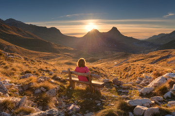 Woman on bench looking out at view of the mountain landscape