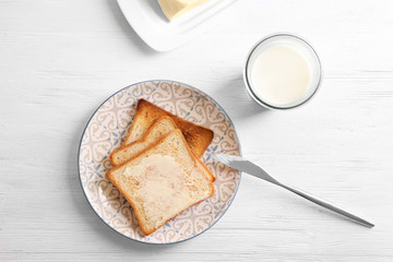 Plate with tasty toasted bread and glass of milk on wooden table