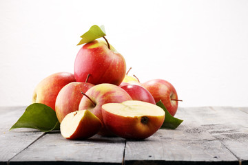 Ripe red apples with leaves on wooden background.