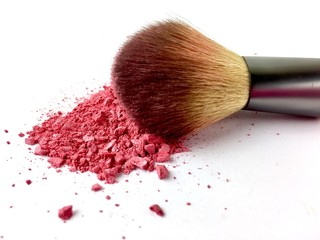 Makeup brush with pink powder blush on a white background