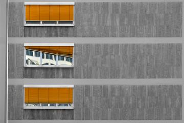 Hausfassade mit Fenster und defekter Jalousie