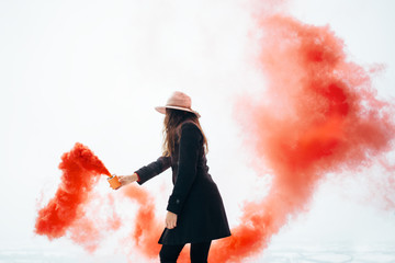 Girl with smoke bomb makes colorful painting