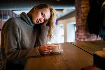 Young beauty woman in a cafe drinking coffee