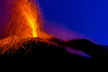 active volcano spraying lava into the night on Stromboli island in Italy