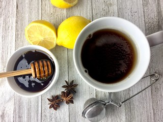 Hot tea with honey and lemon on a rustic wood surface