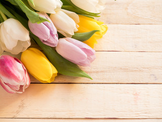 Bouquet of colorful tulips on wooden background Copy space