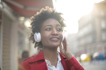 Beautiful girl listening music in the street