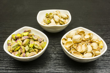 Shelling pistachio nuts. Whole, nutshell and peeled pistachios in bowls.