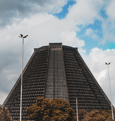 Close-up view of Metropolitan Cathedral of Rio De Janeiro (San Sebastian) made in modernism style; a cloudy bright summer day, with several lanterns, poles, and trees in the foreground