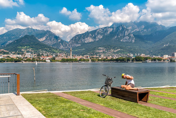 Cyclist resting on the Lakefront of Malgrate located on the shore of Como Lake in province of Lecco.